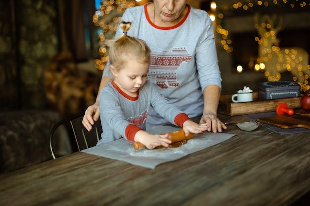 おばあちゃんは孫娘が伝統的なクリスマスジンジャークッキーの生地を出すのを手伝います Premium写真