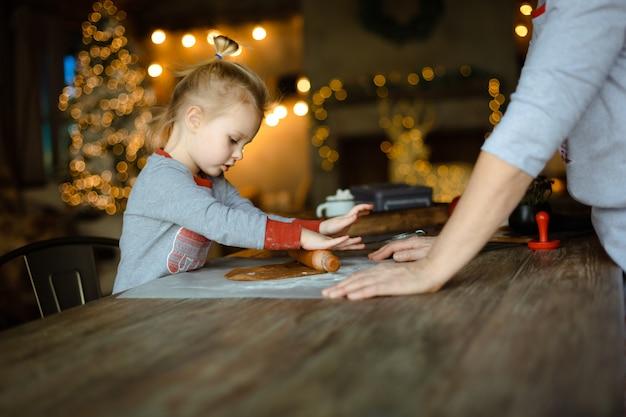 おばあちゃんは、小さな孫娘が伝統的なクリスマスジンジャークッキーの生地を出すのを手伝います Premium写真