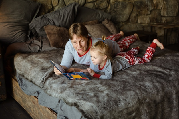 おばあちゃんと孫娘が一緒にベッドで本を読んで楽しんでいます Premium写真