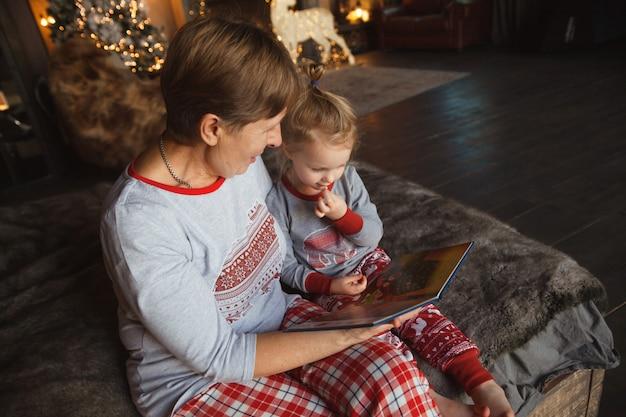 祖母と孫娘はパジャマと本を読んでベッドに座っています。 Premium写真
