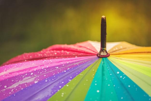 Поверхность радуги зонтик с каплями дождя на нем. Premium Фотографии