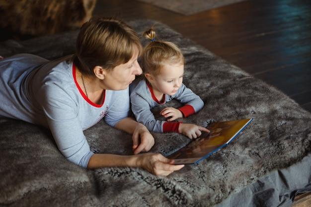 おばあちゃんと孫娘は一緒にベッドで本を読んで楽しんでいます。 Premium写真