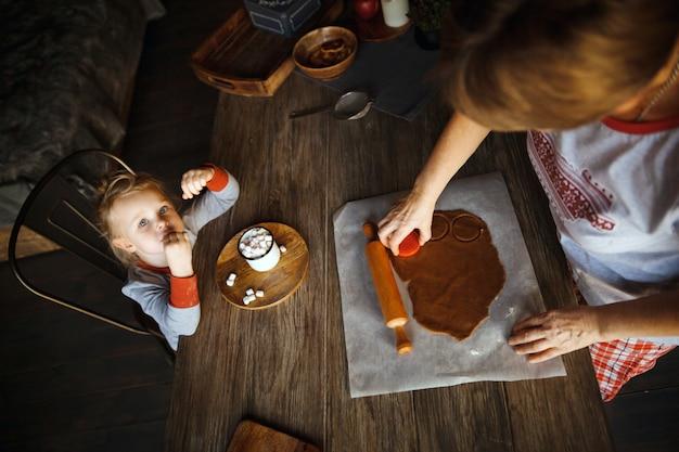 クリスマスの朝。おばあちゃんはジンジャービスケットを作り、孫娘はマシュマロとココアを飲みました。 Premium写真