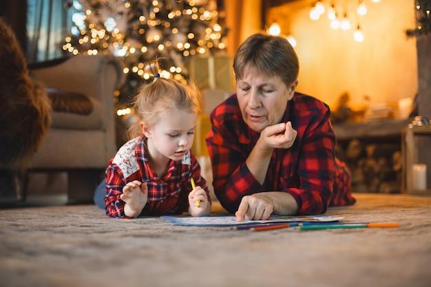 おばあちゃんと孫娘がクリスマスツリーの前のカーペットの上に横たわって描きます。 Premium写真