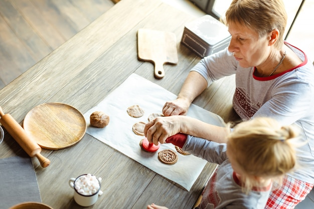 Красивый ребенок и ее бабушка готовят традиционные рождественские печенья по утрам. Premium Фотографии