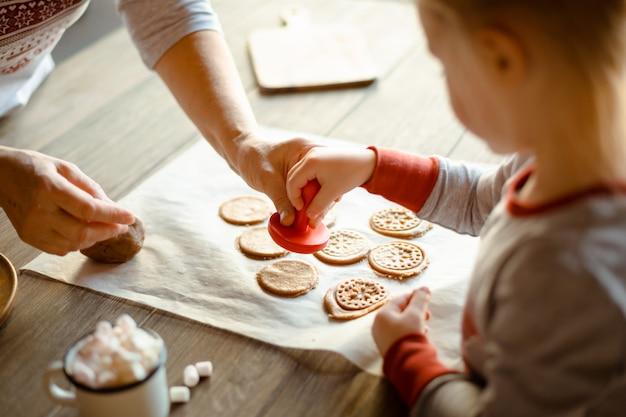 同じパジャマ姿で午前中に祖母と孫娘が一緒にクリスマスクッキースタンプをテストで焼きます。家族の居心地の良いクリスマスのコンセプト。 Premium写真