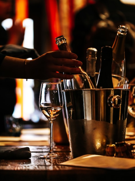 Дегустация вин: на деревянном столе стоит бокал вина и серебряное ведро для охлаждения вина Premium Фотографии