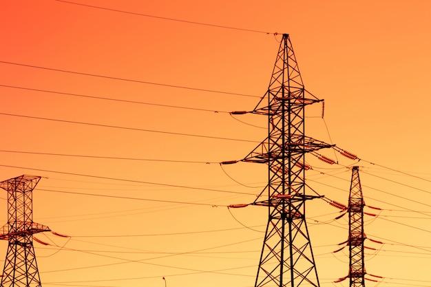 夕焼け空を見下ろす夕方の光と高出力の鉄塔のシルエット。 Premium写真