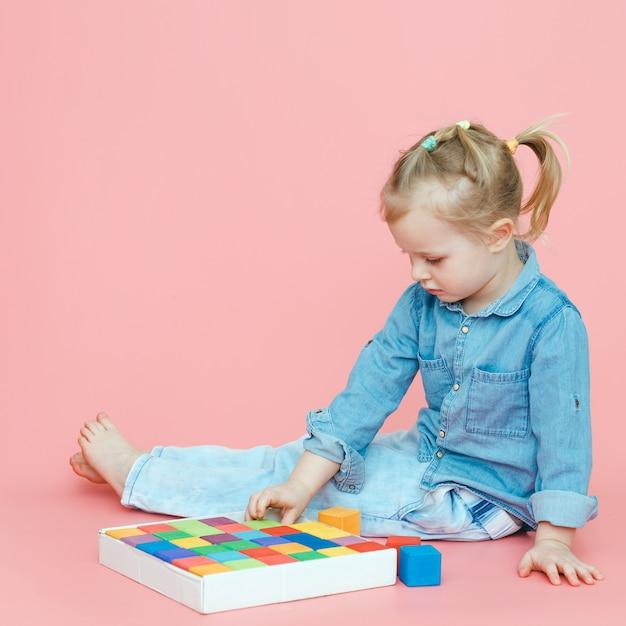 ピンクの背景にデニムの服の魅力的な少女は、白いボックスに木製のマルチカラーキューブを置きます。 Premium写真