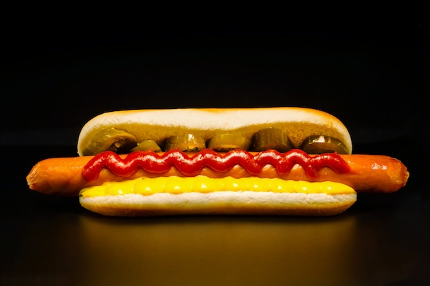 チリペッパーリング、ケチャップ、チーズソースと小麦のパンのおいしそうな長いフランクフルター Premium写真