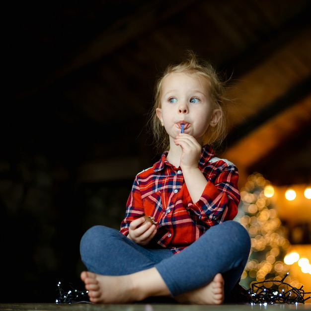 クリスマスに装飾された狩猟家に座っているチョコレートの卵を食べるかわいい幼児の女の子。 Premium写真