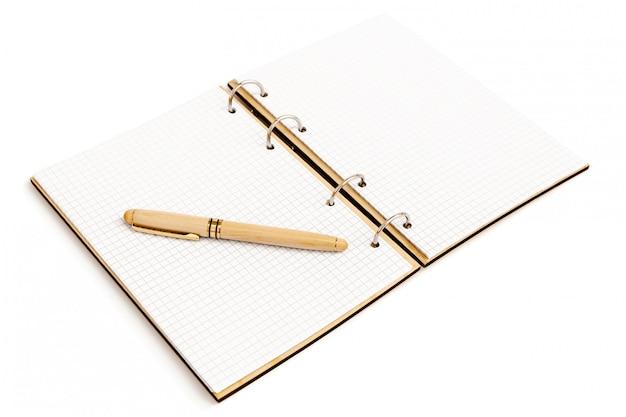 キャップ付きの木製ケースのハンドルは、木製カバー付きの開いているノートブックの空のシートにあります。 Premium写真