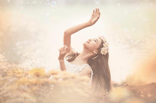 Красивая девушка в винтажном платье и шляпа стоя возле разноцветных цветов Premium Фотографии
