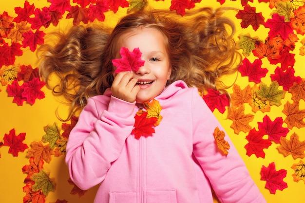 秋のカエデの葉の上に横たわる少女 Premium写真