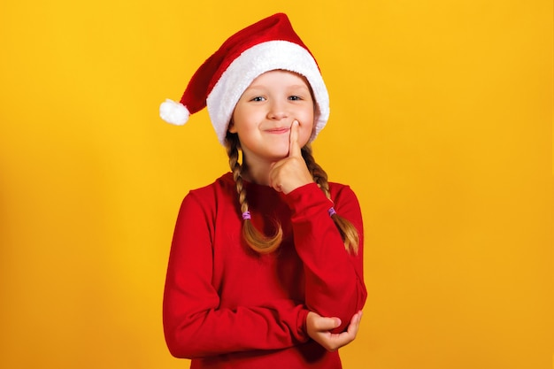 Маленькая девочка в шляпе санта. Premium Фотографии