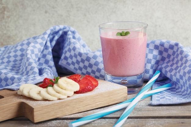 おいしいイチゴとバナナのスムージー、または牛乳を新鮮な果実と一緒に振る。 Premium写真