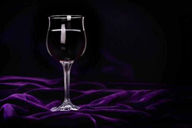 紫の波紋のビロードの生地に赤ワインのガラス。 Premium写真