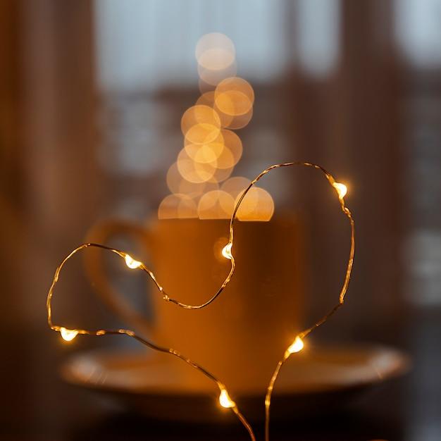 Сложенный из гирлянды сердце на размытой чашке кофе или чая, пар из гирлянды размытым боке. праздничное настроение. размытый. расфокусированный. Premium Фотографии