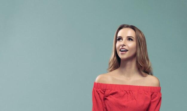 Удивленная девушка носить с плеча и глядя вверх Premium Фотографии