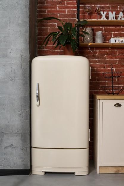 ビンテージキッチンのレトロなスタイルの白い冷蔵庫 Premium写真