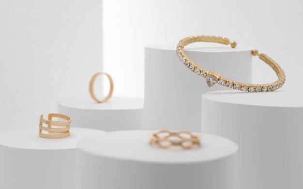 白いプラットフォームにダイヤモンドとリングのコレクションをあしらった美しい貴重なブレスレット。 Premium写真
