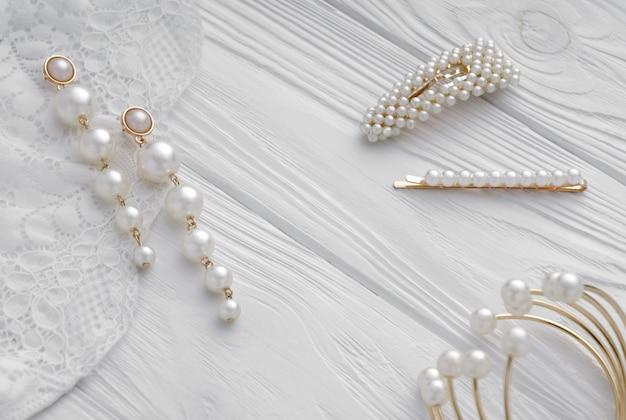 パールゴールデンイヤリング、ヘアピン、白い木のブレスレット Premium写真