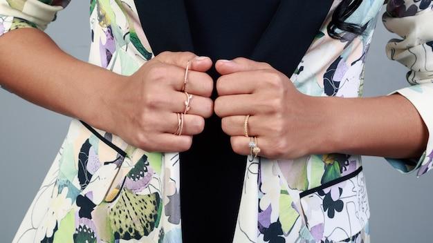 Крупным планом на руках девушки носить золотые кольца и держа жакет с цветочным узором Premium Фотографии