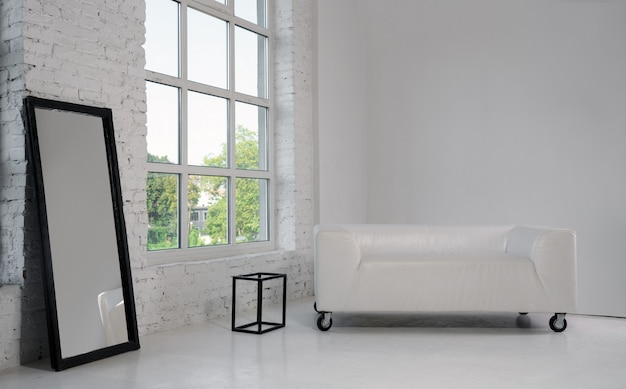 白い部屋の白いソファと大きな黒い額入りミラー Premium写真