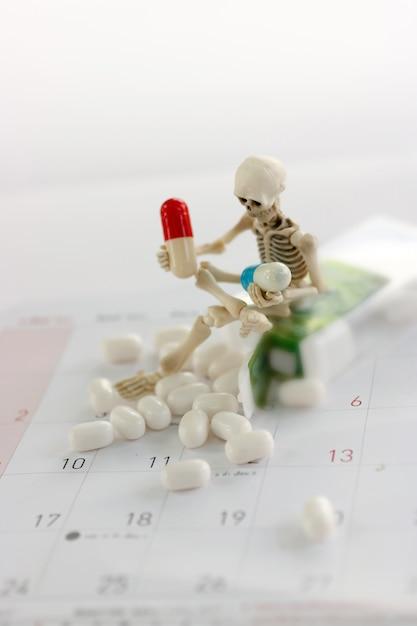 Скелет и наркотики, медицинское здоровье и против концепции лекарств. Premium Фотографии