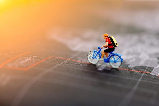 世界地図上でサイクリングするミニチュアの人々。旅行、スポーツ、ビジネスコンセプト。 Premium写真