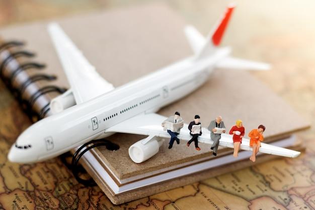 Миниатюрные бизнесмены сидя на самолете с картой мира используя как концепция перемещения и дела. Premium Фотографии