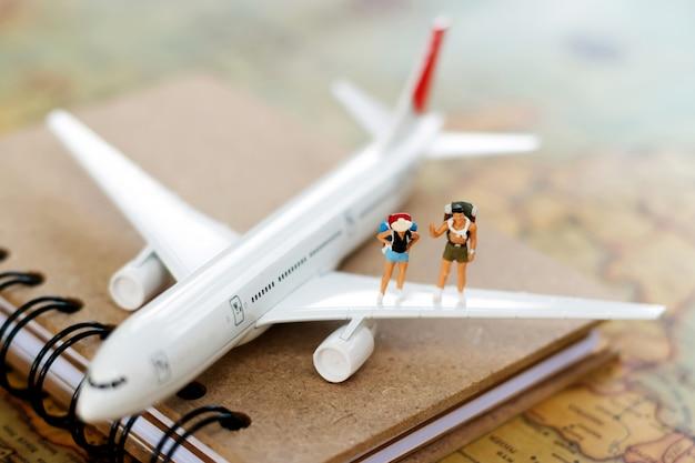 Миниатюрные люди: путешествие с рюкзаком, путешествие на самолете. Premium Фотографии