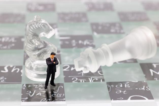 ミニチュアの人々、チェス盤の上に立ってガラスのチェスを持ったビジネスマン。 Premium写真