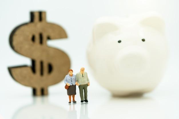 ドル記号と貯金箱で立っている老人のミニチュア Premium写真