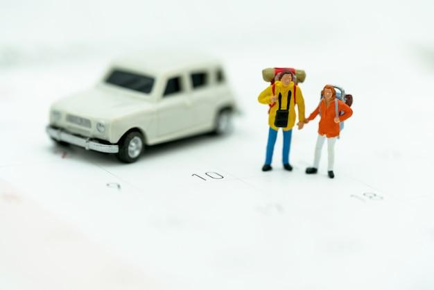 旅行カレンダーの上に立ってバックパックを持つ観光客のミニチュア Premium写真