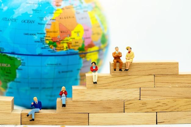 世界の木箱に座っているビジネス人々のミニチュア Premium写真