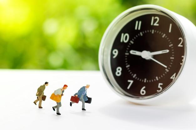 実行している人々のミニチュアは、時計で職場に行く Premium写真