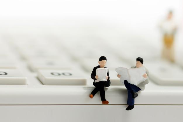 電卓とコインを読んで実業家のミニチュア Premium写真