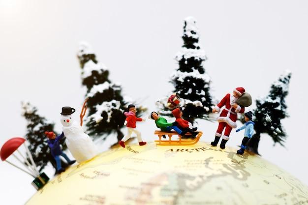 ミニチュアの人々:子供たちは世界中のサンタクロースと雪だるまと一緒に楽しみます。 Premium写真