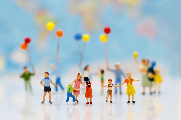 Миниатюрные люди, семья и дети с разноцветных шаров, стоя перед домом. Premium Фотографии
