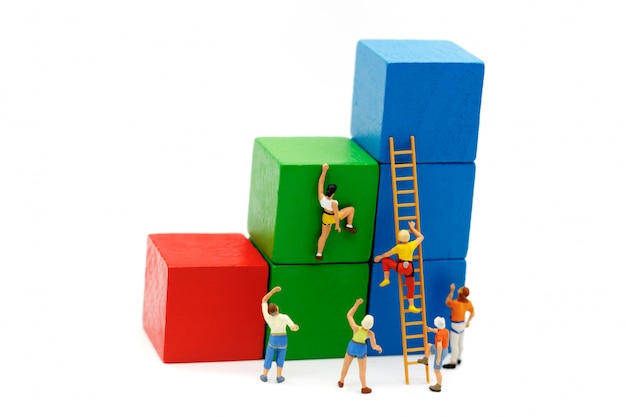ミニチュアの人々:登山家が木製のはしごで成長グラフのルートに挑戦しながら見上げます。 Premium写真