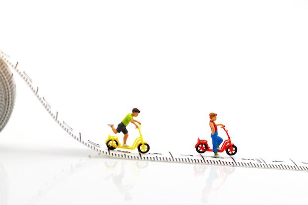 ミニチュアの人々、子供たちが自転車で遊ぶ Premium写真