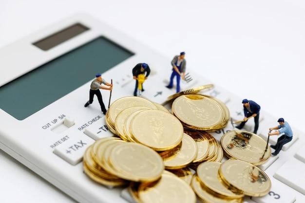 ミニチュアの人々:電卓と黄金のコインに取り組んでいる労働者。 Premium写真