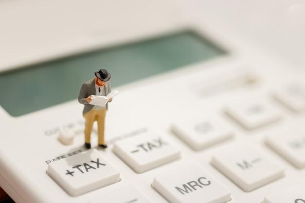 ミニチュアビジネスマンスタンド電卓の税ボタンを読みます。 Premium写真