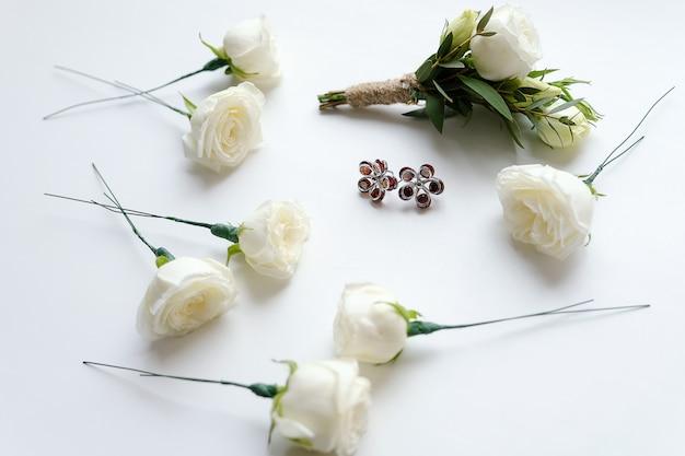 白いバラと緑の葉の新郎のブートニア。花とイヤリングの花嫁の近く。結婚式の道具とアクセサリー。 Premium写真
