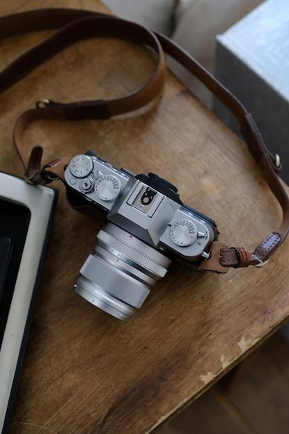 茶色の木製のテーブルの上のビンテージカメラ。次は本です Premium写真