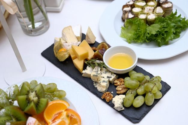 様々な料理をお祝いのテーブルに出す。さまざまな種類のチーズ片、ガラスのボウルに蜂蜜、果物、野菜、ナッツ、ライトテーブルの上の黒いセラミック皿。 Premium写真