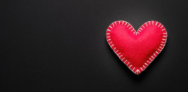 Красное сердце на черном фоне. концепция медицинского страхования, всемирный день здоровья, всемирный день гипертонии, охрана здоровья. Premium Фотографии