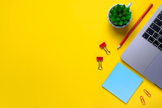 Ноутбук, цветок, наклейки, скрепки, канцтовары на желтом фоне. рабочее место фрилансер, бизнесмен, предприниматель, деловая женщина. баннер. Premium Фотографии