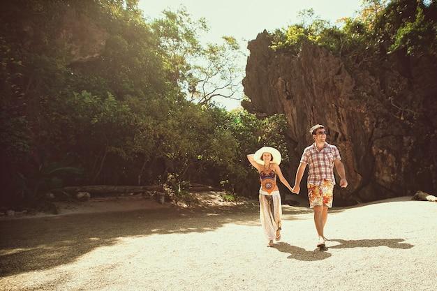 手を取り合って、晴れた日、屋外の山々とビーチの上を歩いて美しい幸せなカップル。帽子と熱帯の国で休暇中の男の女の子。ライフスタイル旅行・観光、新婚旅行 Premium写真
